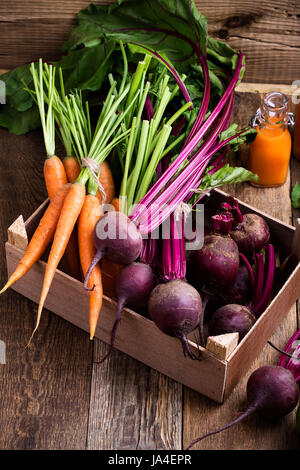 Organic  farm. Fresh vegetables in crate,   beetroots and  carrots on rustic wooden background - Stock Photo