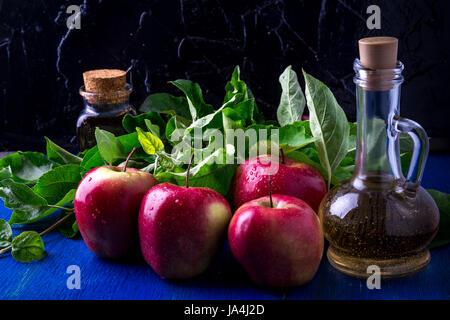 Apple cider vinegar. Three glass bottle on blue background. Red apples - Stock Photo