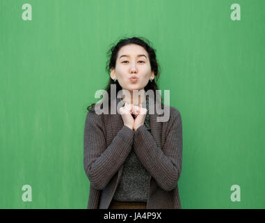 Beautiful Asian girl sends an air kiss. She is standing in a warm sweater near the green wall - Stock Photo