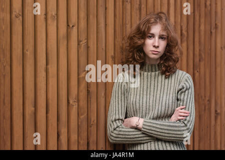A beautiful red-haired girl in a green sweater is standing by the wooden wall. She crosses her arms and looks severely - Stock Photo