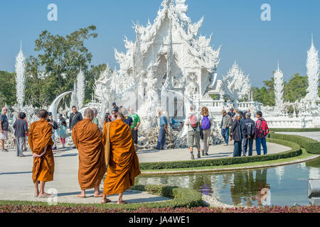 Buddhist monks at ornate Wat Rong Khun (White Temple) in Chiang Rai northern Thailand. This unconventional Buddhist - Stock Photo