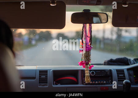 A common sight in Thailand. Phuang Malai -  a flower garland sold for good luck hanging down from the rear-view - Stock Photo