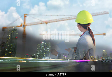Double exposure women asia engineer working and holding blueprints at construction site - Stock Photo