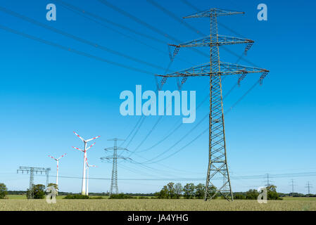 Transmission lines with some wind wheels seen in Germany - Stock Photo