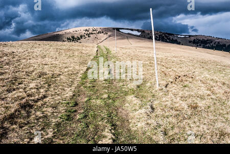 Ploska hill with mountain meadow, hiking trail, few small snow fields and blue sky with dark clouds in spring Velka - Stock Photo