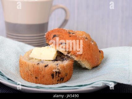 Delicious warm blueberry muffin served with butter and a cup of coffee - Stock Photo