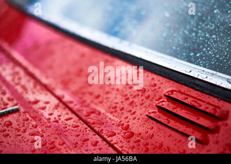 Rain falls on a red car forming water drops, close up of vent and window. - Stock Photo