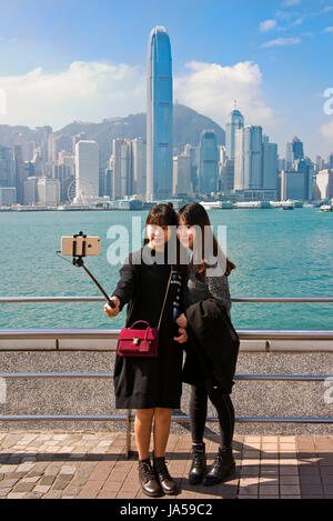 Vertical portrait of tourists taking selfies of the dramatic skyline of Hong Kong Island, China. - Stock Photo