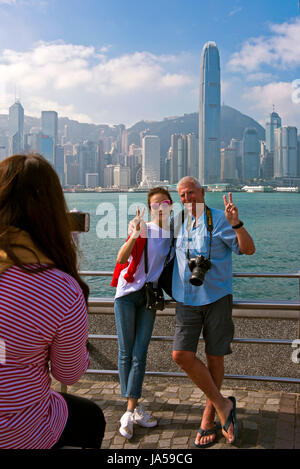 Vertical view of tourists taking photos of the dramatic skyline of Hong Kong Island, China. - Stock Photo