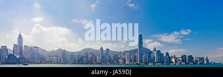 Horizontal panoramic (3 picture stitch) of the dramatic Hong Kong skyline on a sunny day. - Stock Photo