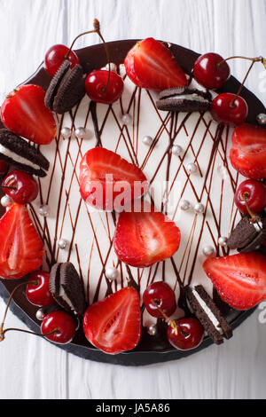 Delicious summer cake with strawberries and cherries, decorated with biscuits close-up on the table. Vertical view - Stock Photo