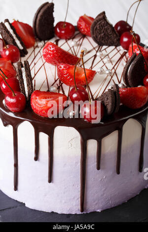 Beautiful cake with strawberry and cherry, decorated cookies and chocolate close-up on the table. vertical - Stock Photo