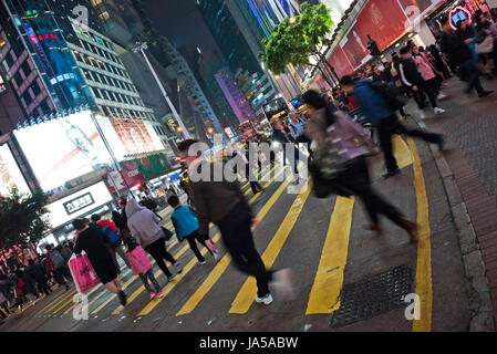 Horizontal view of people crossing the road in Hong Kong, China. - Stock Photo