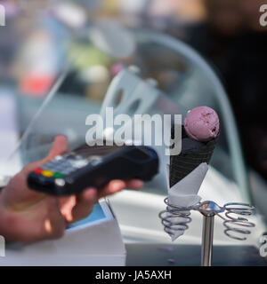Close-up of Stand for Ice-cream. Delicious fresh ice cream in black waffle cone. Purchase with reader machine. Selective - Stock Photo