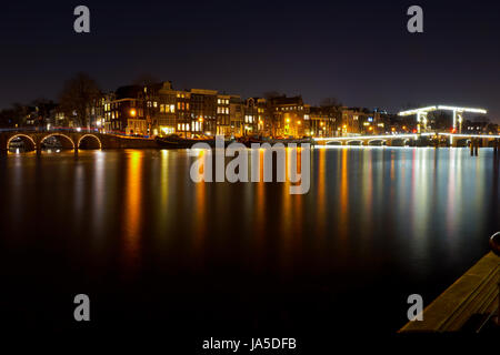 A long exposure of one of the major canals in Amsterdam at night - Stock Photo