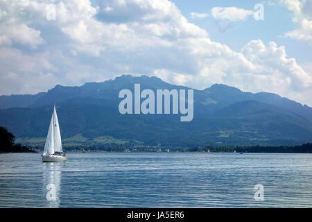 Small sail boat on lake,  with Bavarian alps in background, Chiemsee Upper Bavaria Germany - Stock Photo