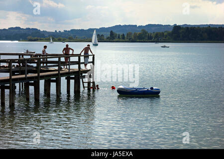Children swimming in Lake with adults on Pier, Chiemsee Upper Bavaria Germany - Stock Photo