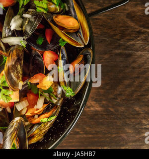 A closeup of a skillet of marinara mussels, shot from above on a dark rustic background with a place for text, square - Stock Photo