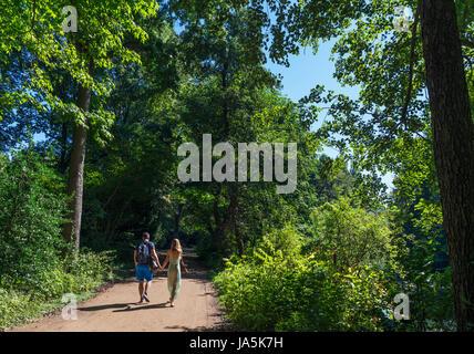 Couple walking along a path in the Tiergarten, Berlin, Germany - Stock Photo