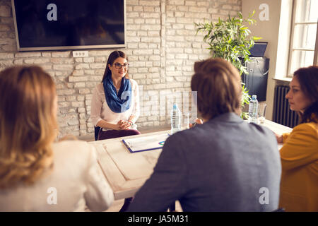 Young female on job interview with commission - Stock Photo