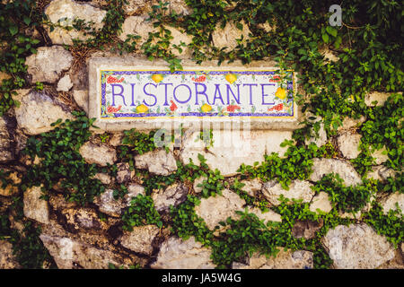 Close up detail of the sign Ristorante on the stone wall in vintage style, Italy - Stock Photo