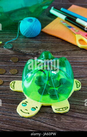 Children's hand-made article from a plastic bottle piggy bank for money. Handmade. Project of children's creativity, - Stock Photo
