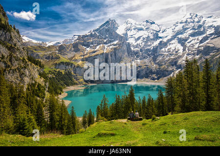 Amazing tourquise Oeschinnensee with waterfalls, wooden chalet and Swiss Alps, Berner Oberland, Switzerland.