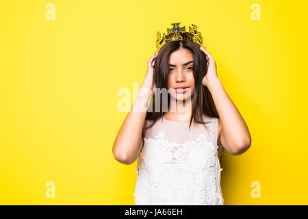 Beautiful young woman wearing crown and nice dress on yellow - Stock Photo
