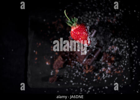 One red straberry on a dark  chocolate, crushed.Coconut chips - Stock Photo