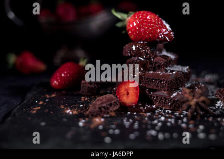 Strawberry lying on a pyramid of chocolate with sliced other strawberries and old silver vase - Stock Photo
