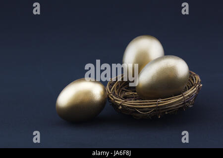 Black background adds drama to success concept of three, gleaming gold nest eggs.  Copy space available on horizontal - Stock Photo
