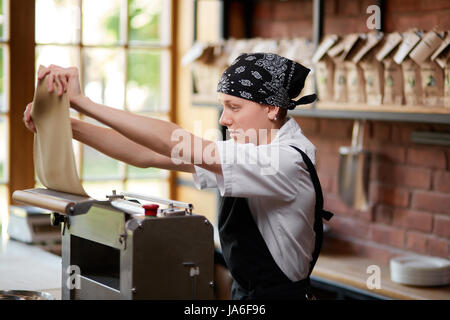 Woman working with dough and pasta rolling machine on the kitchen of restaurant. Making pasta. Making pasta in restaurant. - Stock Photo