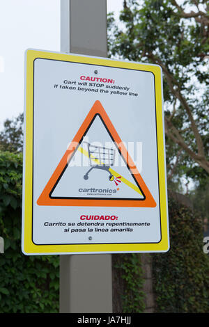 Caution carts will stop suddenly sign. Carttronics a developer of electronic systems used to stop the loss of shopping - Stock Photo