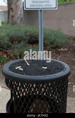 An ashtray for smokers and a designated smoking area sign outside a office building - Stock Photo