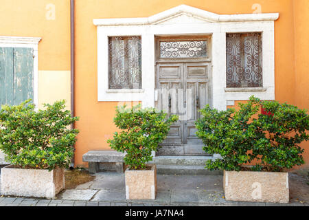 The old entrance door and window with shutters in the wall of an ancient house. Towm on Lake Garda is the largest - Stock Photo