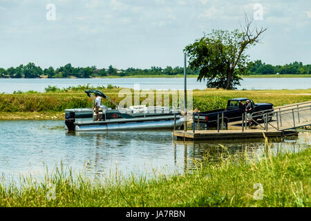 Two men load up a pontoon boat  onto a boat trailer after fishing on Overholser lake in Oklahoma City, Oklahoma, - Stock Photo
