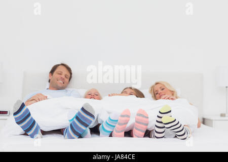 Family wearing stripey socks at home in bed - Stock Photo