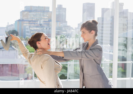 Businesswomen having a massive fight in a bright office - Stock Photo