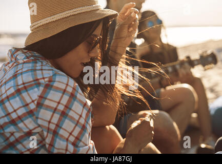 group of friends with guitar on the beach party - Stock Photo