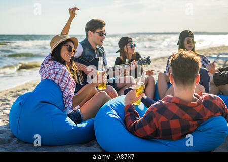 group of friends drinking on the beach party - Stock Photo