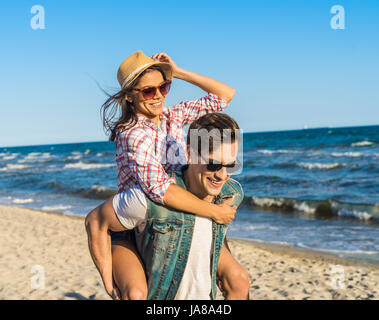 young funny couple in sunglasses piggybacking on the beach. - Stock Photo