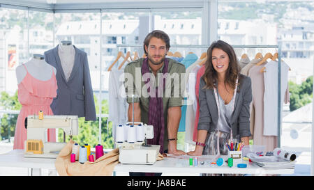 Fashion designers leaning on desk with spools of thread and sewing machine - Stock Photo