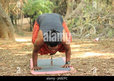 Young Indian man performing the crow pose. (Bakasana) Location - Cubbon Park, Bangalore. - Stock Photo