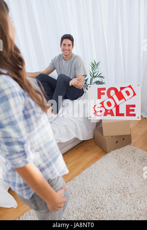 Man chatting with his wife in his new house next to a sign with sold written on it - Stock Photo