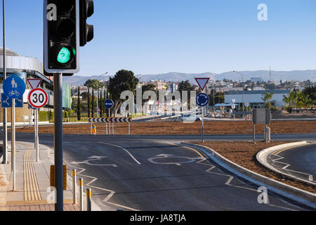 Roundabout with road markings, traffic lights and road signs. Urban scene. - Stock Photo