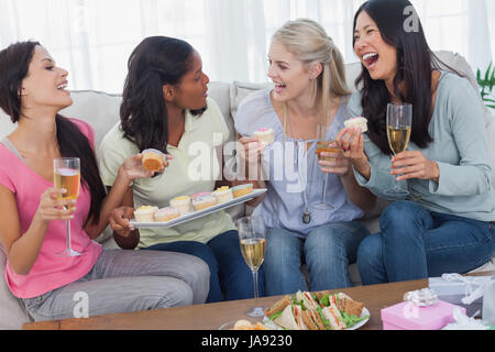 Friends drinking white wine and sharing cupcakes at party at home on couch - Stock Photo