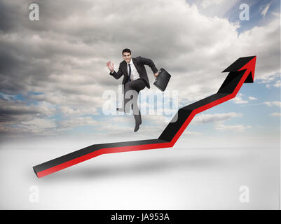 Businessman jumping over a red arrow pointing up with blue sky on the background - Stock Photo