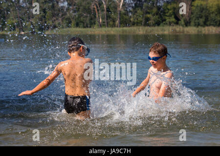 Kids Swimming In A Lake kids jumping, swimming and playing with water in a polish lake