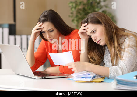 Two worried coworkers reading a letter with bad news in a desk at office - Stock Photo
