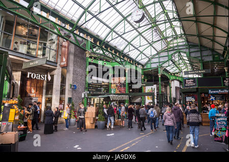 LONDON - OCTOBER 31, 2016: Visitors browse the stalls at Borough Market, home to one of the largest and oldest markets - Stock Photo